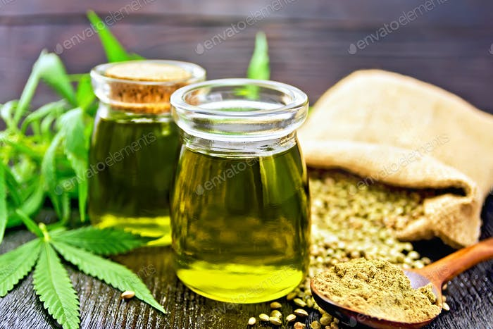 Oil hemp in two jars and flour in spoon on wooden table