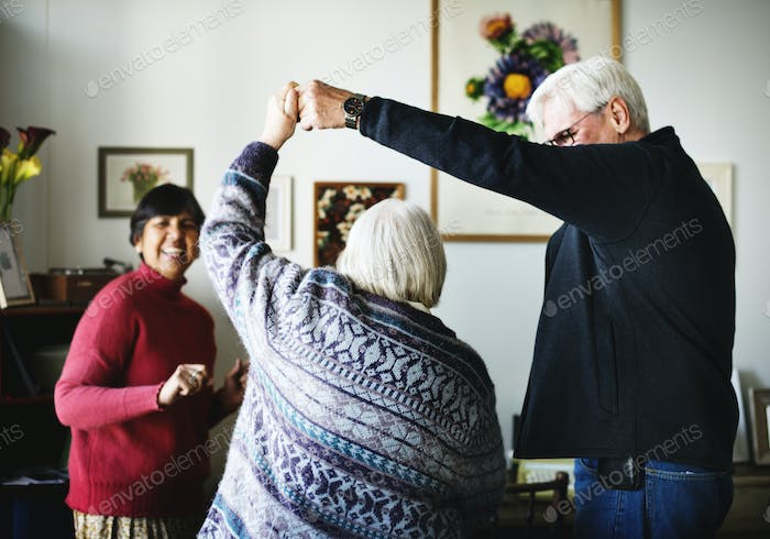 A senior couple dancing in a room
