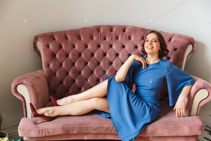 Young cheerful woman sitting indoors