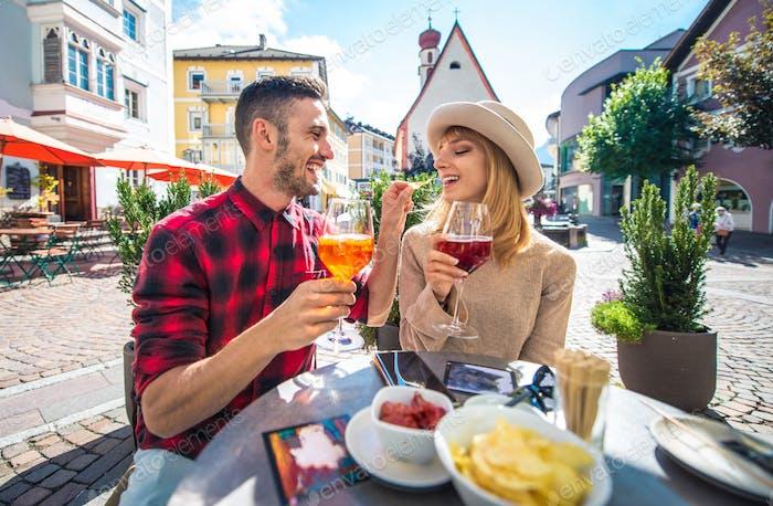 Happy couple taking an aperitif in a cafè.