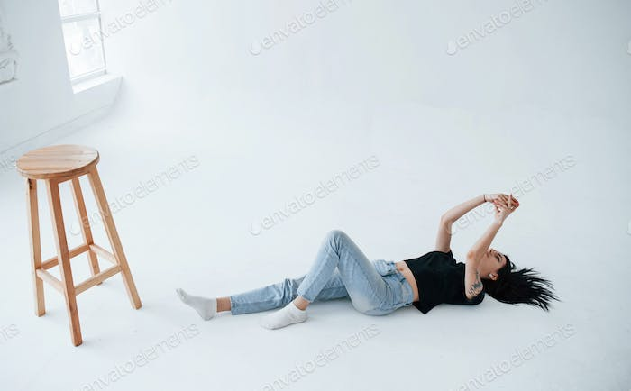 Young female brunette teen have photoshoot in the studio at daytime