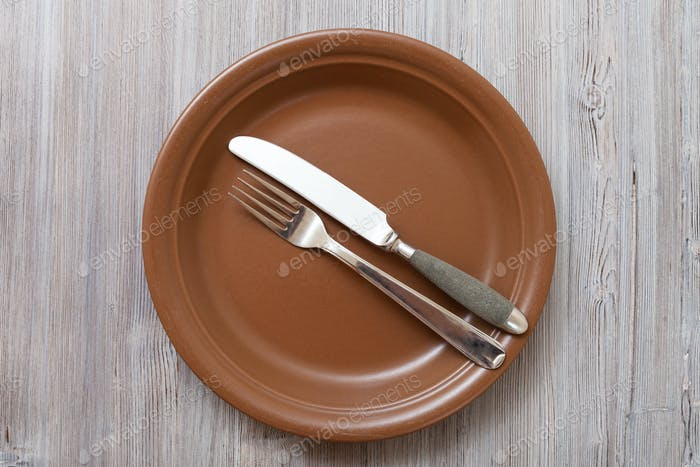 top view of brown plate with flatware on gray