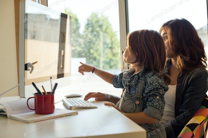 Мама и дочь используют компьютер