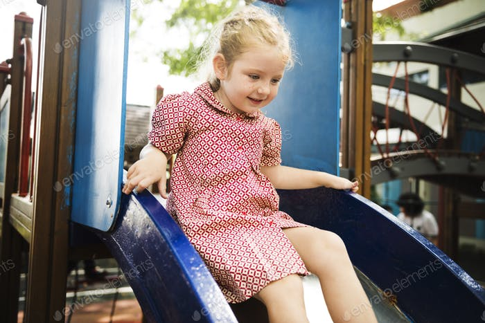 Young girl playing slide in playground