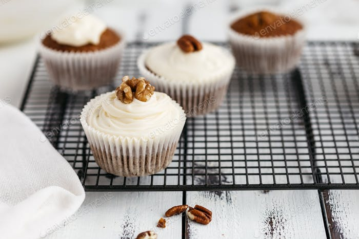 Carrot Cupcakes Decorated with Cream Cheese Frosting and Nuts