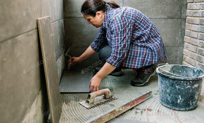 Weibliche Handarbeiterin Verlegung eines neuen Fliesenboden