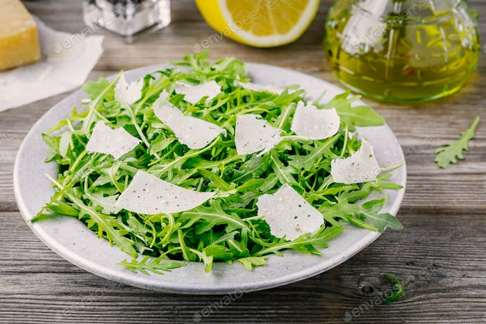 Green arugula salad with Parmesan cheese, lemon, olive oil and seasonings