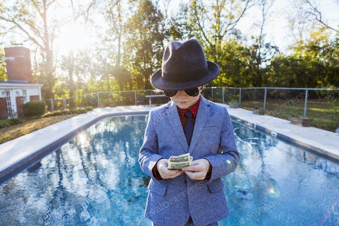 Junge in einem Anzug und dunkle Brille stehen am Rande des Wassers Zählen Dollarscheine.