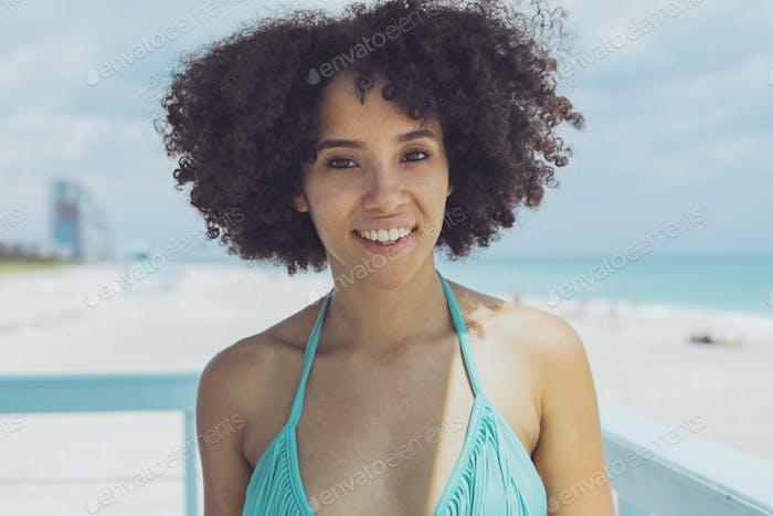 Cheerful black woman in sunlight on beach