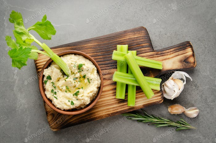 Hummus dip dish topped with chickpeas and olive oil served with celery slices