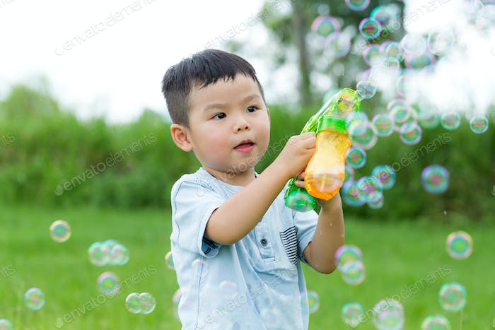 Small kid play with bubble blower