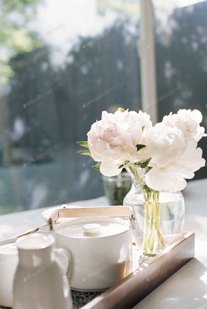 Tablett mit einer Teekanne und einer Vase mit weißen Rosen.