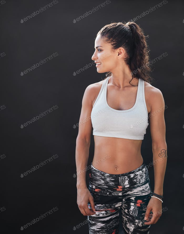 Sportswoman with muscular body on black background