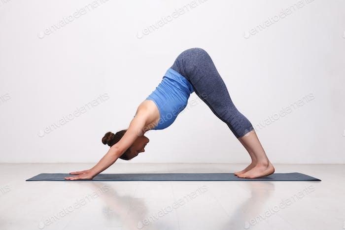 Beautiful sporty fit yogi girl practices yoga asana adhomukha sv