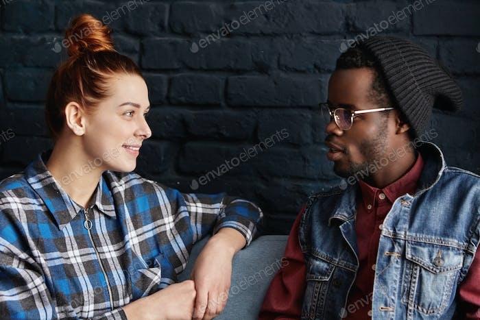 Young interracial couple having date at modern cafe sitting against black brick wall background, loo