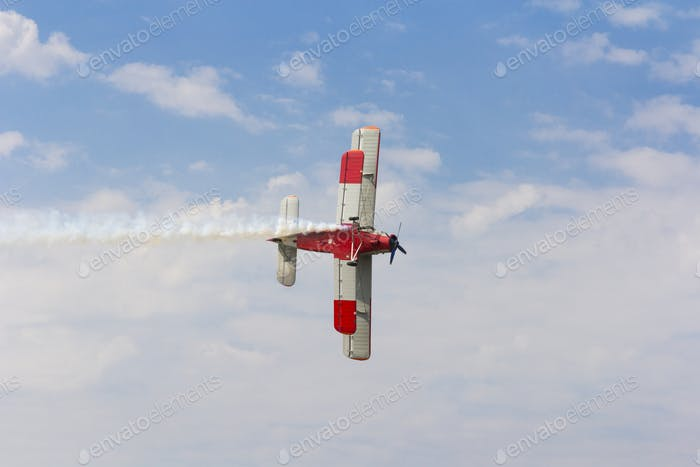 Aircraft AN-2 in a turn against the sky with clouds