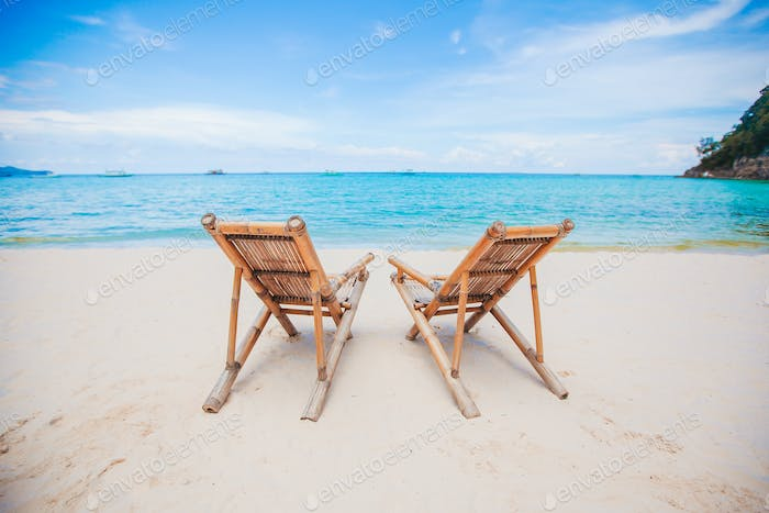 White lounge chairs on a beautiful tropical beach