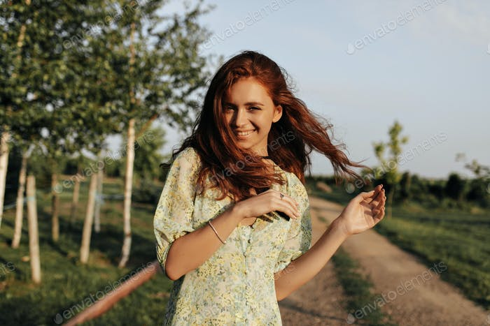 Cheerful lady with long red hairstyle and bandage on neck in summer fashionable dress smiling and l