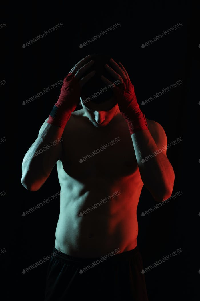Portrait of male boxer posing in red and white light