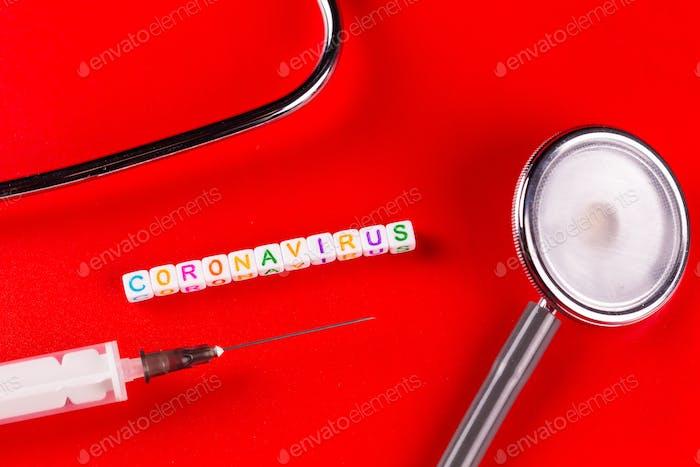Text phrase Coronavirus and syringe on red background.