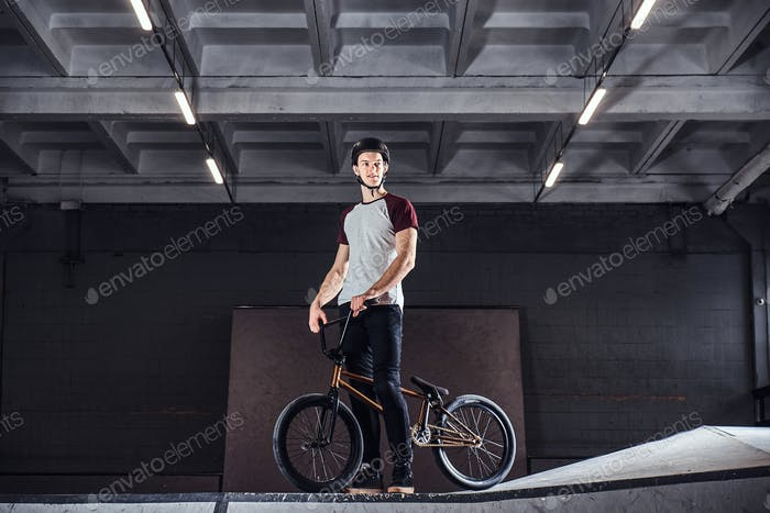 Young man with BMX getting ready to jump in a skatepark indoors