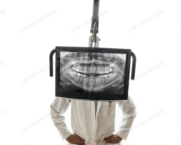 A closeup of a monitor with a dental x-ray and a dentist standing behind the monitor.