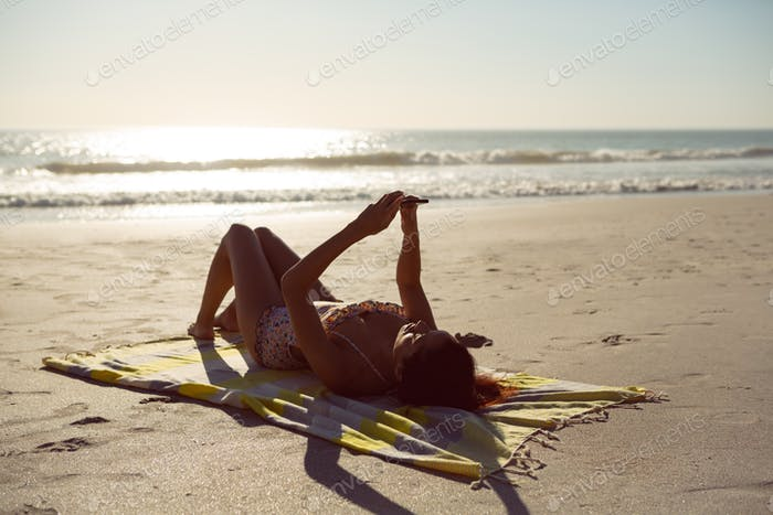 Caucasian woman using mobile phone while relaxing on picnic blanket at beach