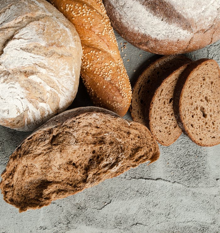 Different types of bread on the concrete top.