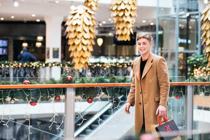 A portrait of teenage boy walking in shopping center at Christmas.