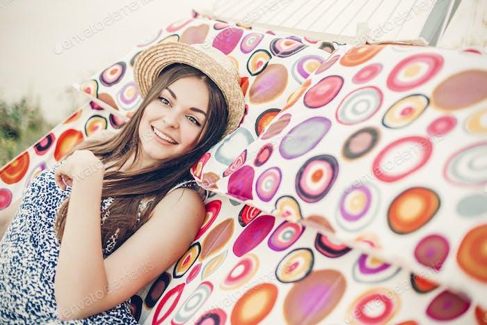 Schöne emotionale Hipster Mädchen zum Ausdruck bringen Freude beim Entspannen in einer Hängematte