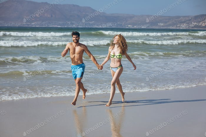 Couple holding hands and running by the ocean at beach on sunny day