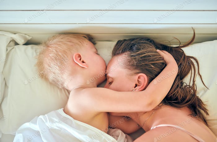 Toddler boy sleeping on pillow with mother