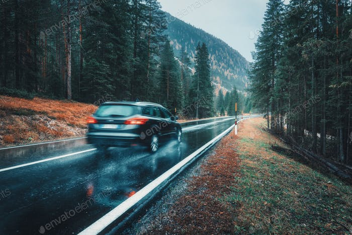 Blurred car in motion on the road in autumn forest in rain