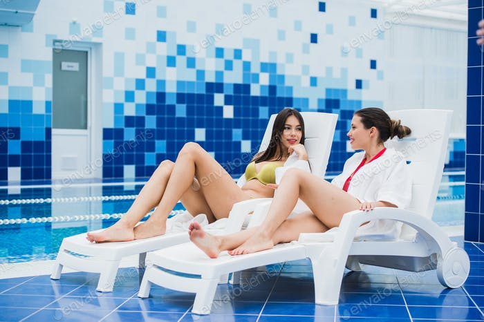 Friends dressed in bathrobes and bikini relaxing at spa next to a swimming pool