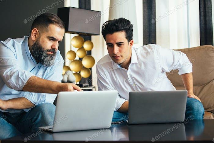 Serious men looking at laptop