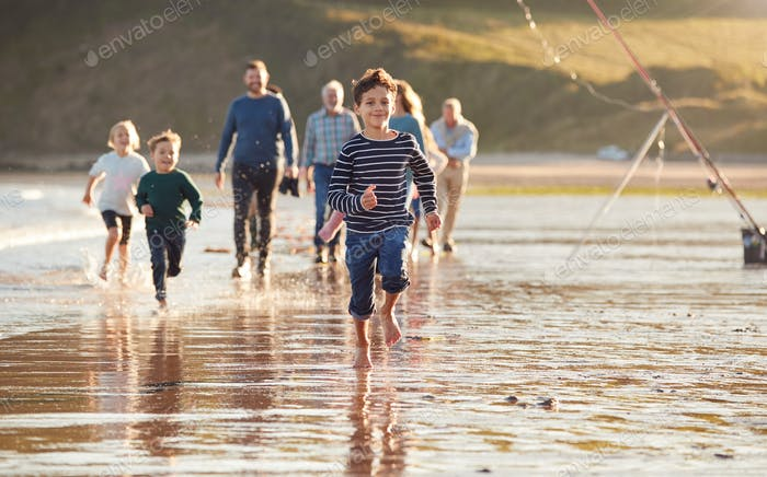 Children Run Ahead As  Multi-Generation Family Walk Along Shore On Winter Beach Vacation