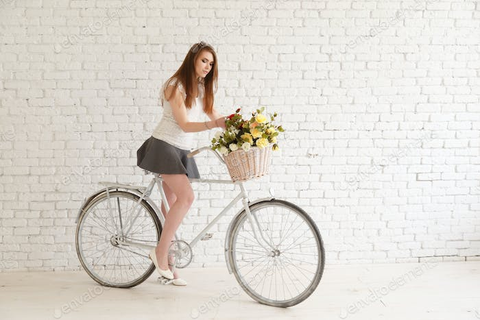 Lovely girl with a bike and basket of flowers on background white brick wall.