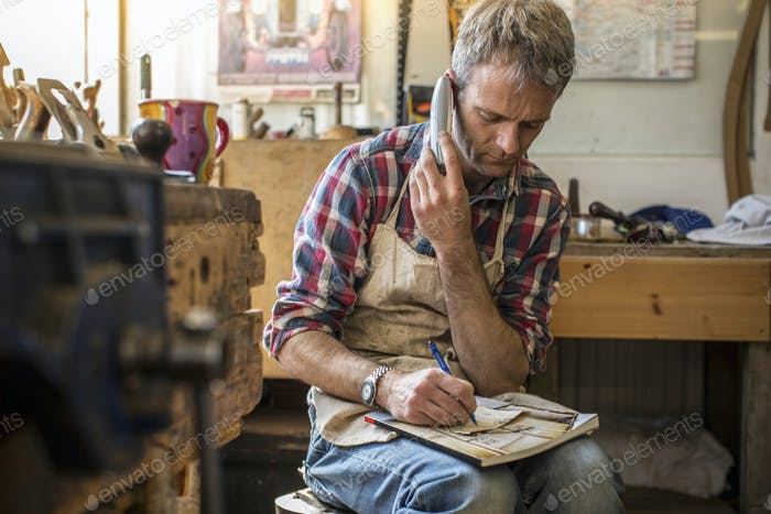 An antique furniture restorer in his workshop, using a smart phone.