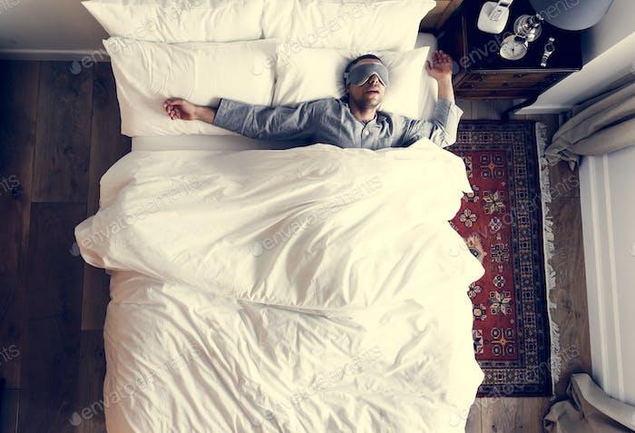 Mann auf Bett schlafen mit einer Augenabdeckung