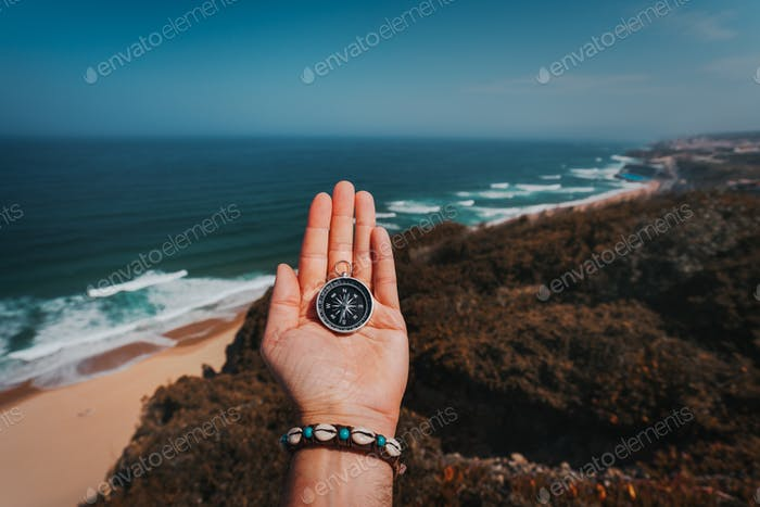 POV man hand with compass. Symbolling adventure-seeking concept against sea and waves in coastline