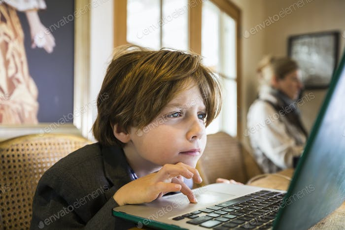A six year old boy typing on a laptop at home, using the cursor touch pad.