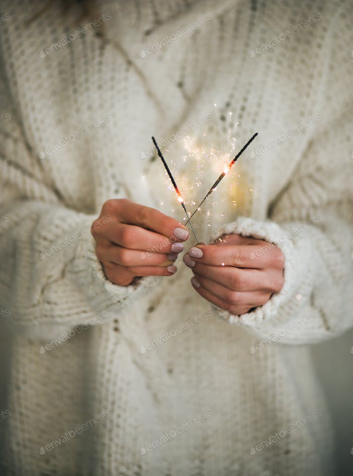Woman in sweater holding Christmas sparklers in hands, close-up