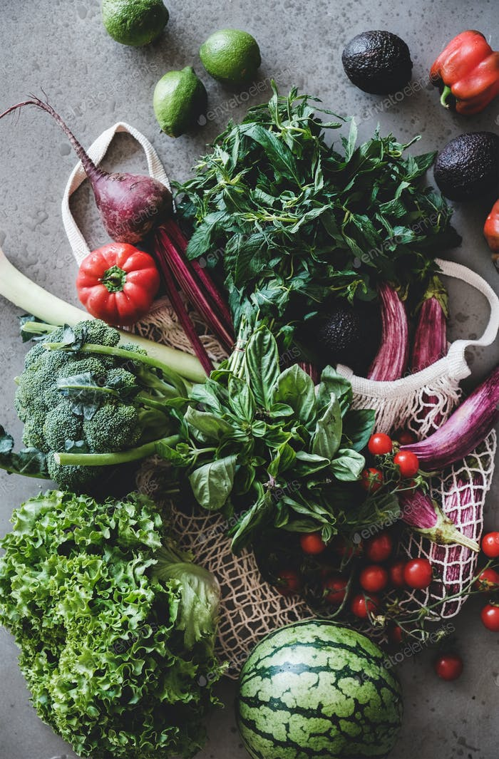 Fresh vegetables, greens and fruits over concrete kitchen counter