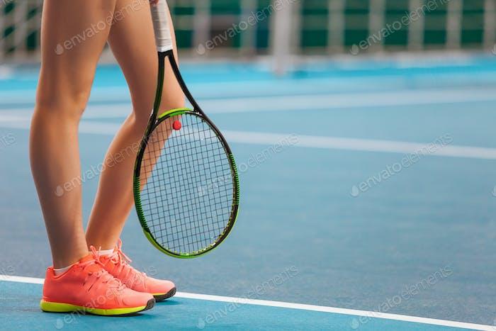Beine des jungen Mädchens in einem geschlossenen Tennisplatz mit Schläger