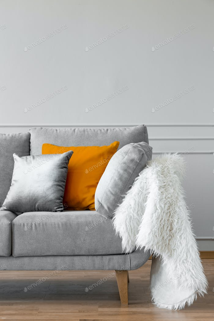 Orange pillow and fur on grey settee in bright minimal apartment interior. Real photo
