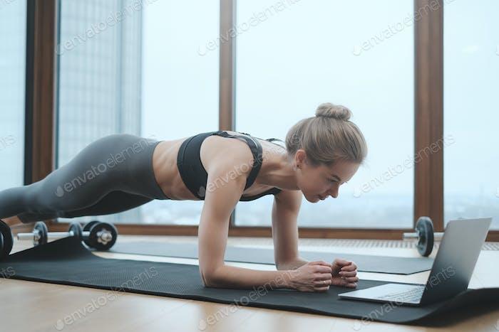 Deportista caucásica en el apartamento hacer yoga con ordenador portátil