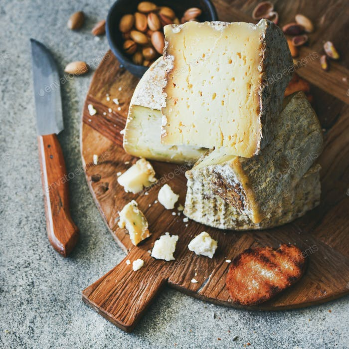 Cheese platter with nuts, honey and bread, square crop