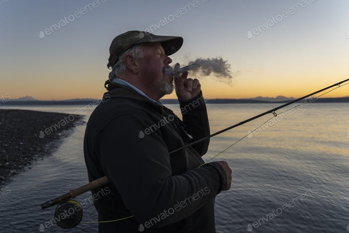 A caucasian senior fly fisherman enjoys a sunrise cigar before fly fishing for searun coastal