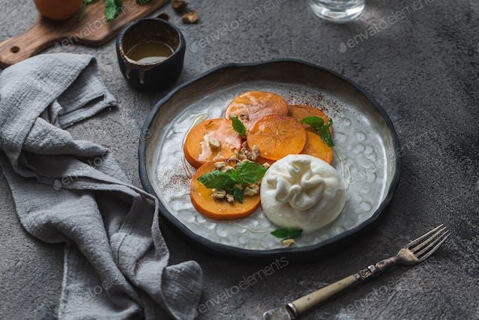 Buratta Käse mit Persimmon serviert auf handgefertigtem Teller