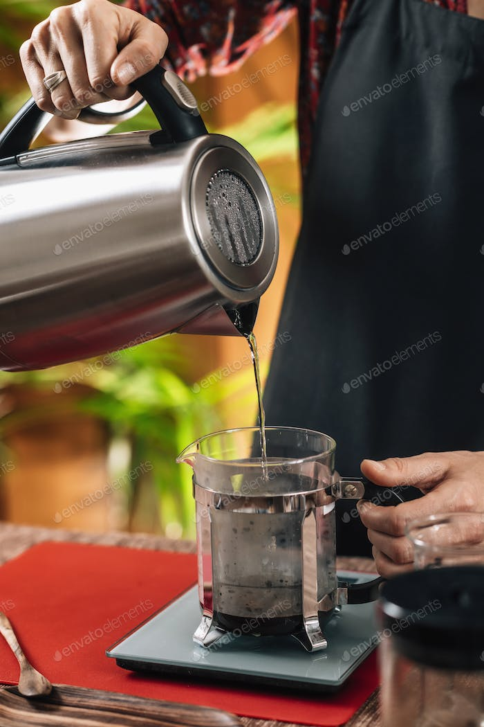 French Press Coffee.  Barista Pouring Boiling Water From Kettle